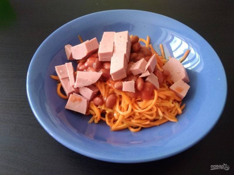 3. Колбасу нарежьте кубиками, тоже добавьте в салатницу.