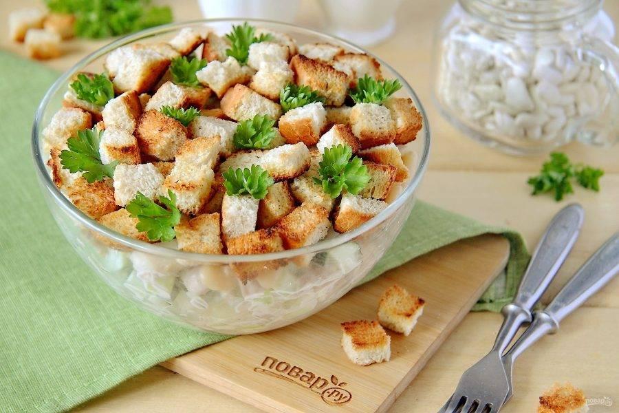 Перед подачей посыпаем салат сухариками и свежей зеленью. Салат с фасолью, копченой курицей и сухариками готов. Приятного аппетита!