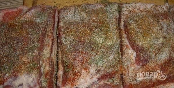 На беконе сделайте надрезы. Натрите его всеми специями и солью. Оставьте мариноваться на ночь в холодильнике.