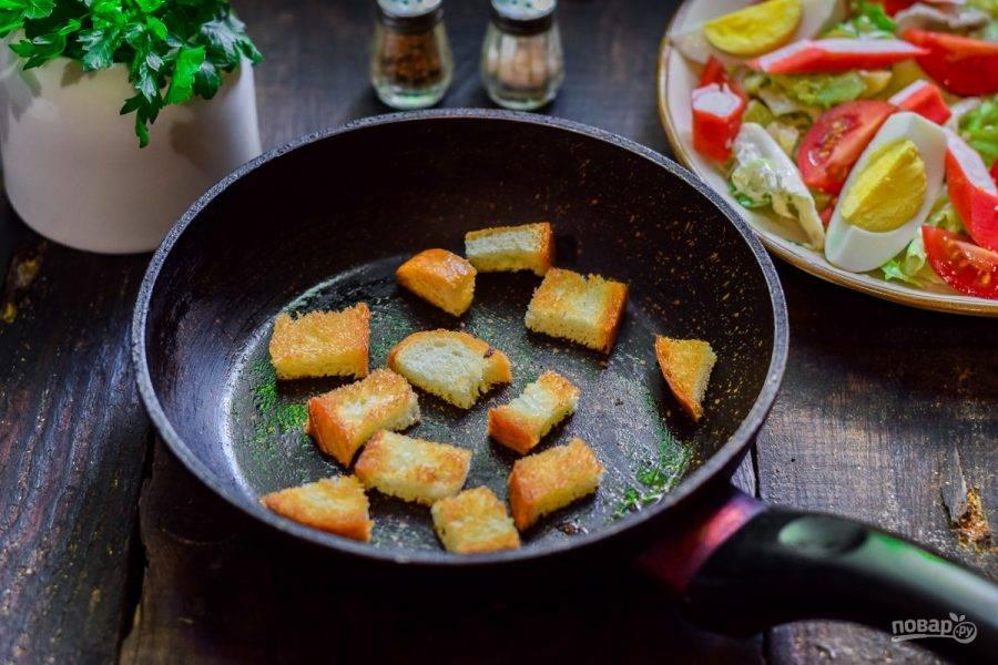 Батон нарежьте кубиками и подсушите в сковороде. По желанию посыпьте специями и сухим чесноком.