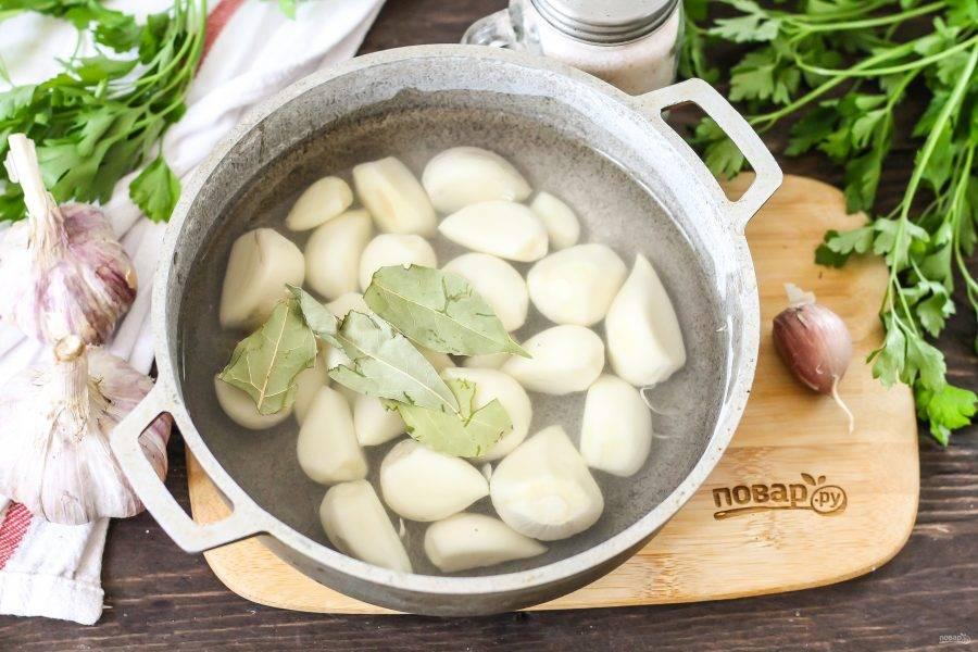 Высыпьте зубчики в казан и залейте горячей водой. Добавьте лавровые листья и отварите примерно 1-2 минуты.