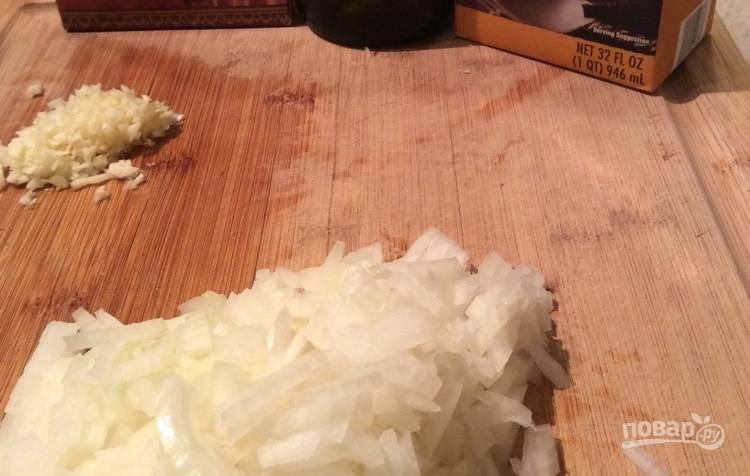 1.Влейте куриный (овощной) бульон и белое сухое вино в кастрюлю, поставьте на огонь и доведите до кипения на небольшом огне, затем уменьшите огонь и сохраняйте температуру. Почистите и измельчите лук и 3 зубчика чеснока.