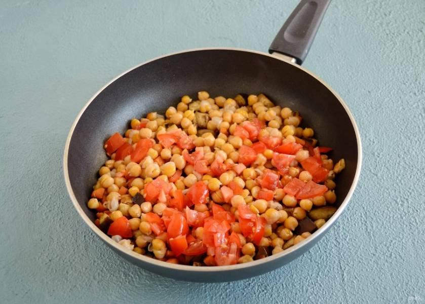 Затем добавьте варёный нут с небольшим количеством воды и помидоры, перемешайте, накройте крышкой и тушите еще несколько минут.