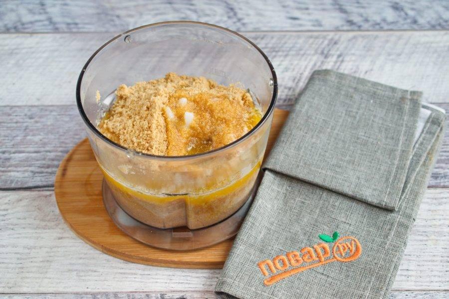 Измельчите печенье в крошку, добавьте растопленное сливочное масло, перемешайте до однородности.