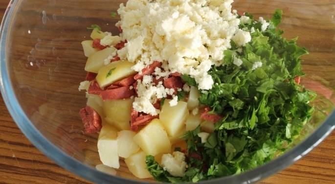 3. Высыпаем в емкость картофель с колбасой, туда же отправляем нарезанную петрушку и натертый сыр.