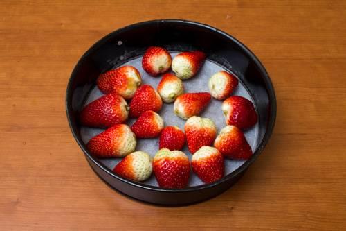 4. Форму для выпечки застелить пергаментом. Ягоды вымыть, обсушить и выложить на дно. Если ягоды крупные, можно разрезать половинками. Кисленькие ягоды можно немного подсластить.