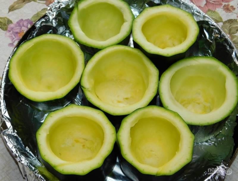 Кабачки разрежьте на кусочки толщиной в 4-6 см. Ложкой извлеките середину, не доходя до низа и формируя чашечки. Поставьте их на противень для запекания.