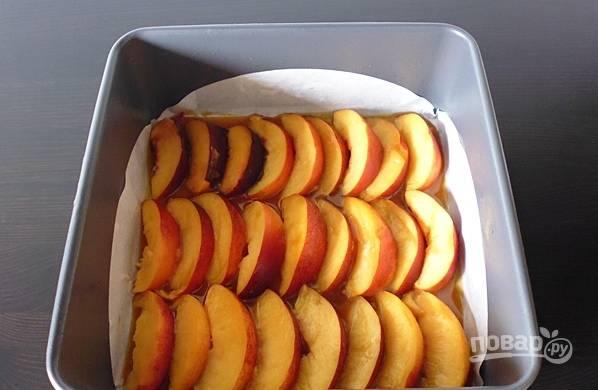 Персики помойте, нарежьте тонкими дольками и аккуратно выложите на карамель.