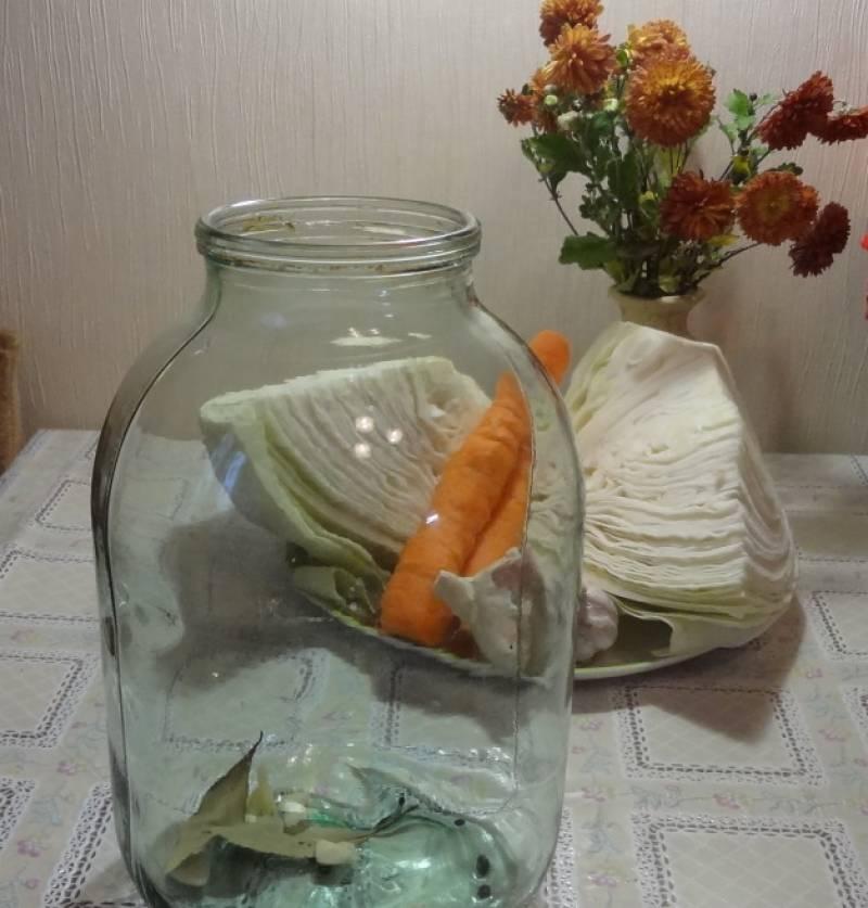 1. В трехлитровую стерильную банку выкладываем все специи, кроме соли, сахара и уксуса. Морковку режем кружочками, капусту - средними кусками.