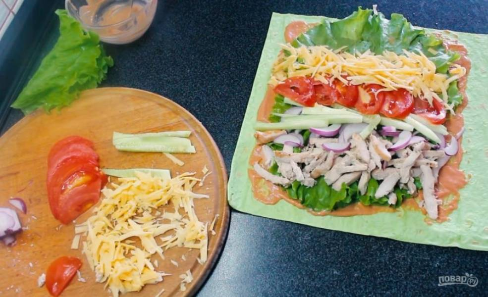 3. Далее выложите всю начинку, чередуя ее: нарезанные полосками отварную или запеченную курицу и огурец, нарезанные полукольцами лук и помидор, натертый на крупной терке сыр.