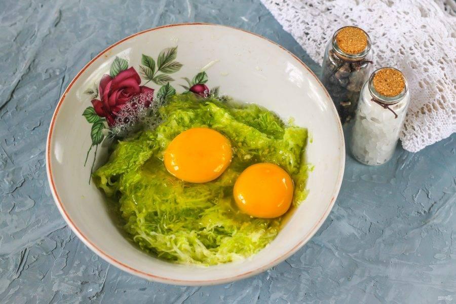 Вбейте в кабачковую массу два куриных яйца, влейте воду и поперчите. Взбейте все вместе.