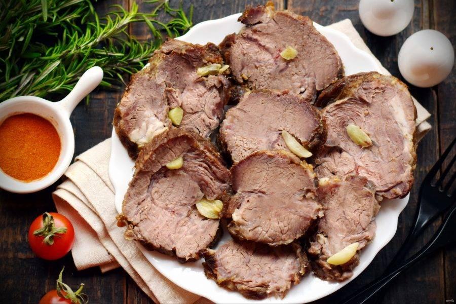 После остывания мясо достаньте из рукава, слейте мясной сок. Буженину нарежьте на порционные кусочки, подайте на стол. Приятного аппетита!
