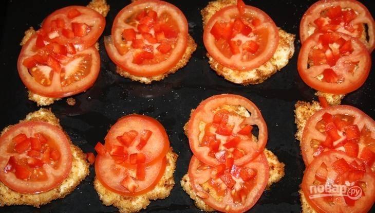 Затем переложите обжаренные кусочки курицы на противень. Вымойте и обсушите помидоры. Нарежьте кружочками и по одному колечку выложите на мясо. Также сверху присыпьте мелко нарубленным сладким болгарским перцем.