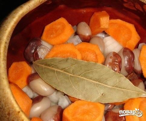 Морковку поскоблите ножом и тщательно вымойте. Нарежьте ее на кружочки толщиной в полсантиметра. Разложите морковь по горшочкам. В каждый горшочек добавьте по одному лавровому листику.