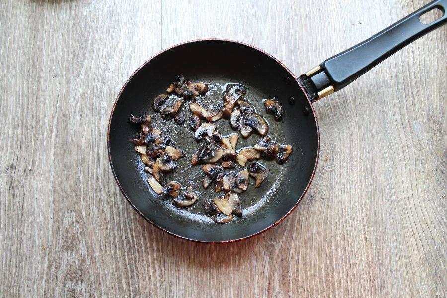 Шампиньоны протрите сырой чистой тканью, удаляя загрязнения и порежьте на пластинки. В сковороду выложите сливочное масло и шампиньоны. Обжаривайте все в течение 5 минут.