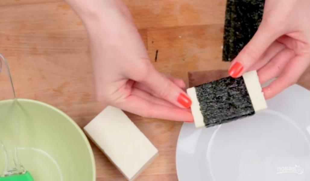 2. Нори разрежьте на полоски чуть тоньше кусочков сыра. Смочите нори водой и аккуратно заверните в них сыр. Проделайте так со всеми кусочками сыра.