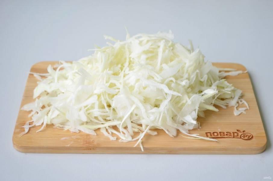 2. Нарежьте ножом тонко капусту. Положите в кипящий суп.