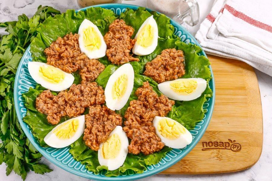 Вскройте консервы, и аккуратно выложите тунец на листья салата между яичной нарезки. Можно использовать как кусочки рыбы, так и стружку в масле. Масло не выливайте, полейте им салат в конце.
