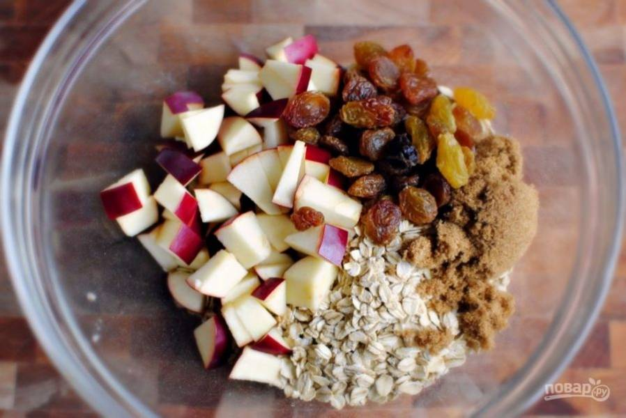 В миске смешайте геркулес, яблоко, изюм и сахар.