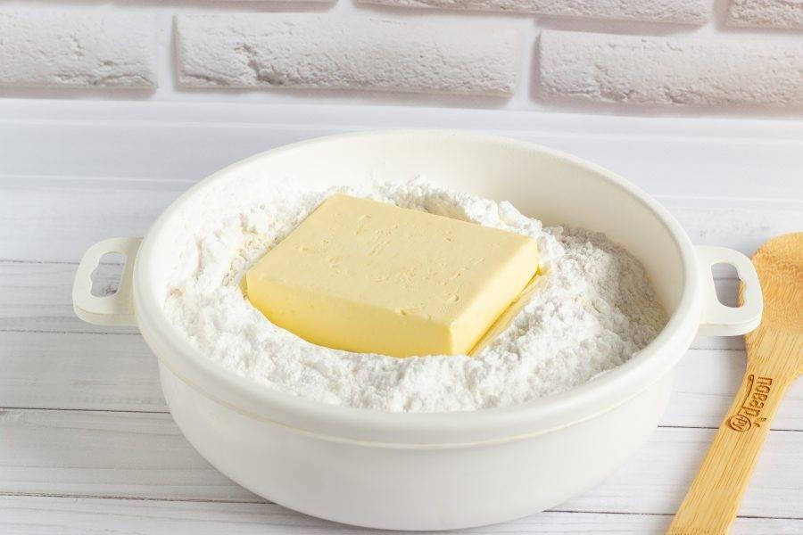 В сухую миску просейте муку, сахарную пудру и разрыхлитель. Добавьте холодное сливочное масло.