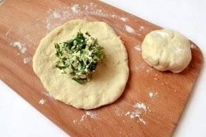 Скатываем тесто в колбаску, разрезаем на 6 частей. Разминаем каждый кусок теста в лепёшку, кладём начинки такое же количество, сколько было теста.