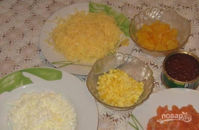 Яйца отварите вкрутую. Отдельно натрите белки и желтки. Мякоть апельсина без плёнок нарежьте. Сыр натрите на крупной тёрке. Филе сёмги нарежьте небольшими кусочками.
