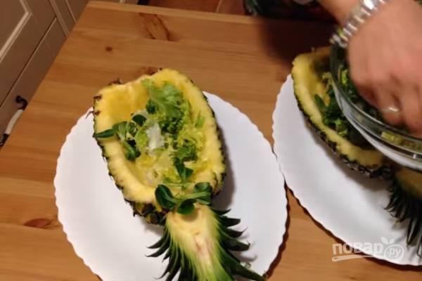 На дно ананаса выложите промытый и немного измельченный (любым удобным для вас способом) салат.