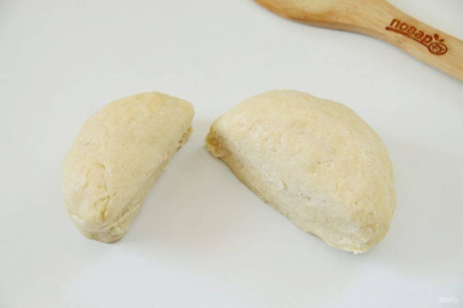 Достаньте тесто и разделите его на две части. Одна должна быть чуть больше другой.
