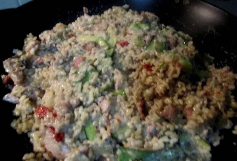 Как только кабачок и грибы станут мягкими, выключаем огонь и выкладываем на сковороду с рисом обжаренную курицу с беконом, а также измельченные томаты. Добавляем йогурт по вкусу (консистенция ризотто должна быть кремообразная), досаливаем при необходимости и перемешиваем все.