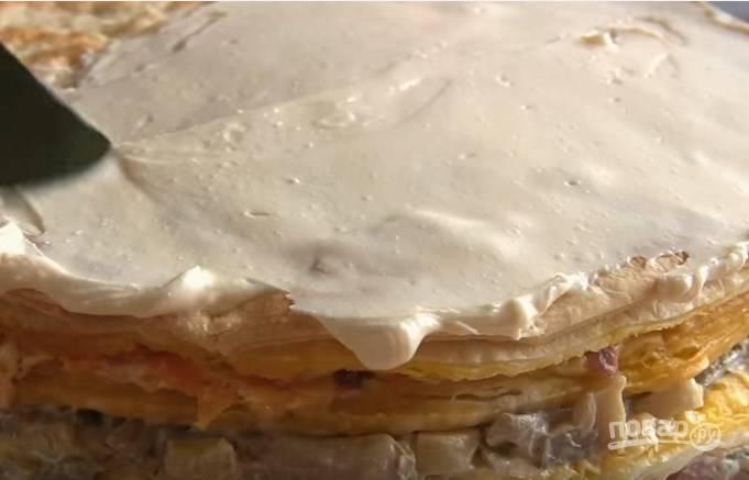 7. Смешайте 150 г плавленого сыра с майонезом, этим кремом намажьте верх и бока торта. Отправьте его на сутки в холодильник.