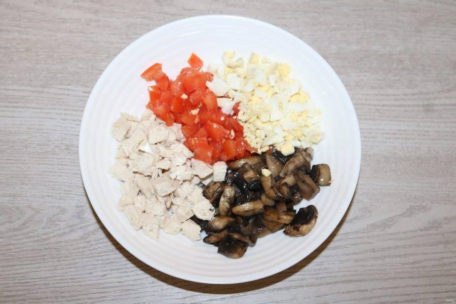 В салатнике соедените нарезанное куриное филе, яйца, помидор, обжаренные шампиньоны.