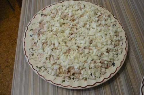 3. Поверх майонеза - слой яичных измельченных белков. Их мы смазываем майонезом более обильно, а также салат по бокам.