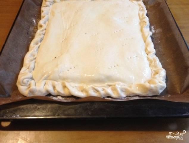 Вторую часть теста также раскатайте, укройте ею сверху начинку, скрепив по краям с основой. Молоко взбейте с яйцом, промажьте этой смесью верх и бока пирога.
