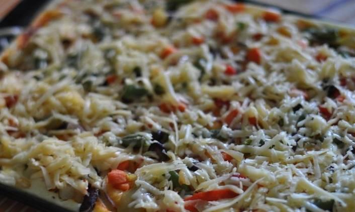 Ставим противень в разогретую до 180 градусов духовку и выпекаем пиццу минут 8-10, затем извлекаем противень и посыпаем пиццу тертым сыром, отправляем ее в духовку еще буквально на минутку.