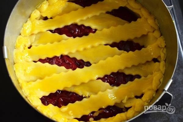 Оставшееся тесто раскатайте с тонкий пласт, разрежьте на полоски и выложите их сверху начинки. Смажьте верх пирога слегка взбитым желтком.