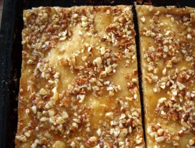 Разрежьте корж на 2 части. Одну обильно смажьте кремом, сверху положите вторую часть и выложите остальной крем. Сверху можно посыпать орехами. Дайте торту немного пропитаться и подайте на стол.