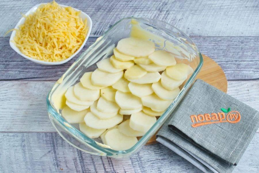 Выложите дно формы для запекания ломтиками картофеля внахлест, полейте 1/2 части соуса, посыпьте половиной тертого сыра Чеддер.