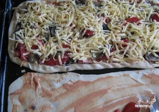 Нарежьте колбаску, сосиску, помидоры, с которых можно предварительно снять кожуру. Твердый сыр натрите на терке. Идеально подойдет Гауда. Смажьте тесто майонезом и кетчупом. Выложите начинку и присыпьте сыром. Также насыпьте ароматные специи.