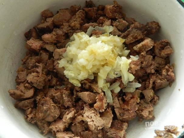 Остывшую печень нарезаем небольшими кусочками и добавляем к ней большую часть поджарки из чеснока и лука.