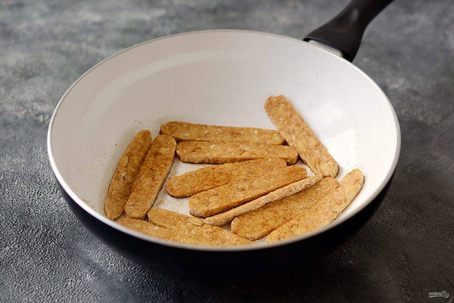 Темпе предварительно отварите 15 минут, затем нарежьте полосками. Обжарьте его с соевым соусом и копченой паприкой до золотистого цвета.