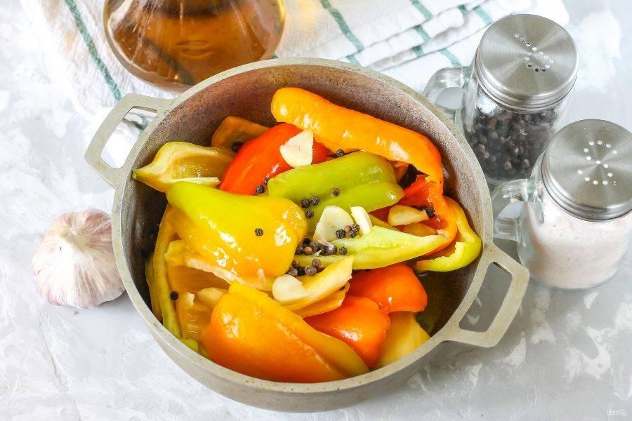 Выложите ломтики перца в казан, всыпьте горошины черного перца. Очистите и промойте чесночные зубчики, разрежьте их и добавьте в емкость.