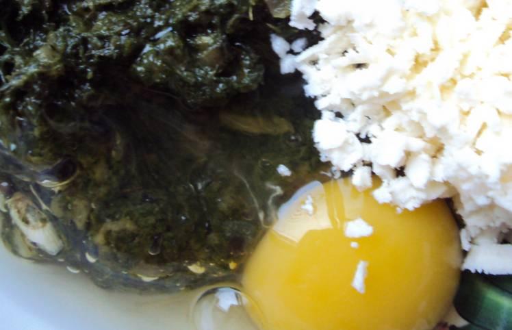 Измельченный репчатый лук обжарьте на масле до мягкости. Добавьте мелко порезанный шпинат, соль, перец и чеснок (пропущенный через пресс). Через 2-3 минуты снимаем его с огня, даем ему остыть. Подмешиваем яйцо и тертый сыр.