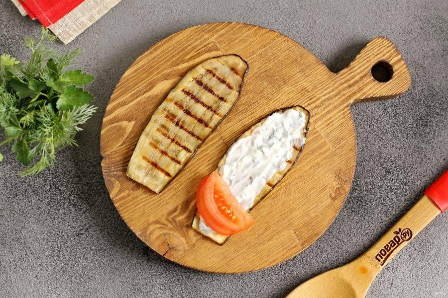 Каждую полоску баклажана смажьте соусом и посолите. На край выложите 1-2 дольки помидора и сверните закуску в рулет.