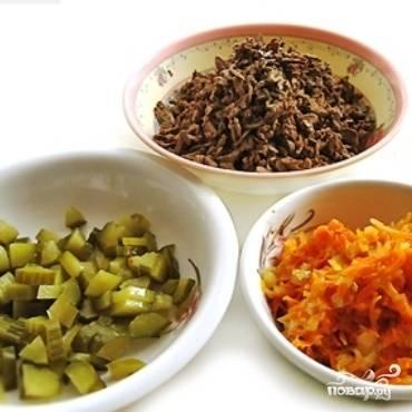 Подготовим все ингредиенты: говяжью печень отварить до готовности и крупно натереть, огурцы нарезать мелким кубиком, морковь натереть и обжарить с мелко нарезанным луком до мягкости.