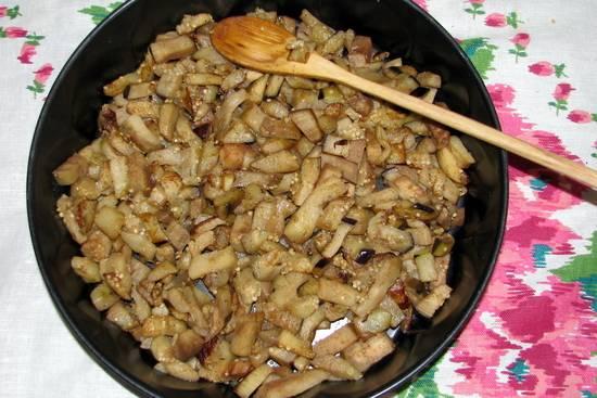 Баклажаны режем кубикам  и обжариваем на растительном масле, 7-8 минут, соль и перец по вкусу. Затем перекладываем их в форму для запекания.