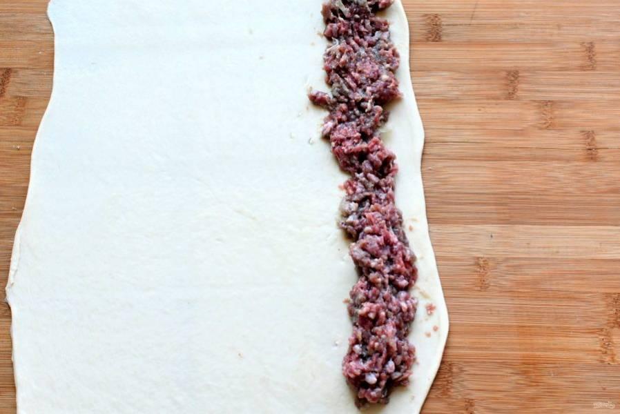 Раскатайте часть теста в тонкий пласт. Выложите по длинному краю дорожку из мясного фарша. Заверните край.