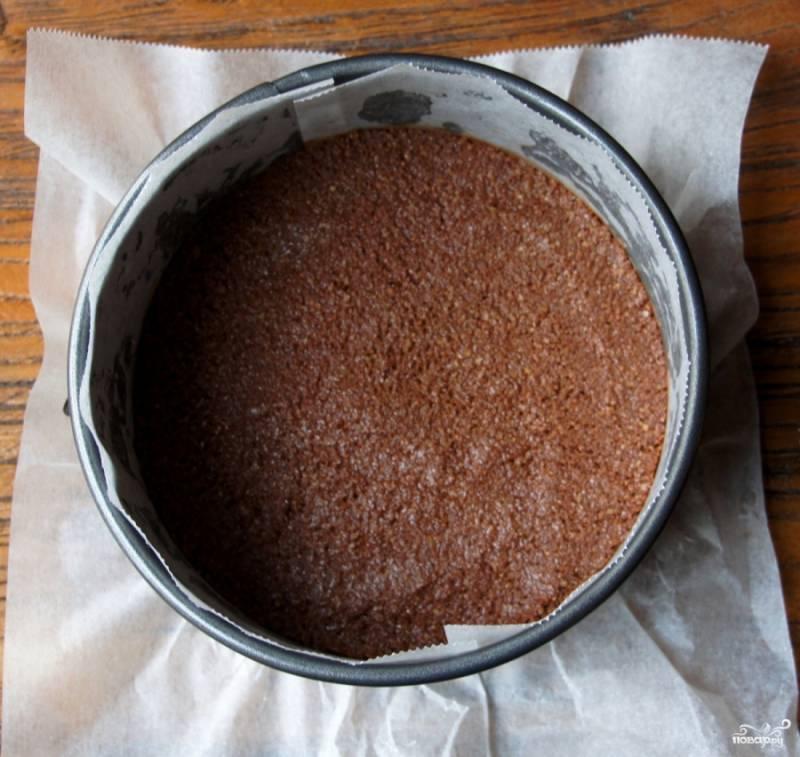 В форму для выпекания (лучше всего диаметром в 24 см) выстилаем бумагу для выпекания, смазываем ее маслом и выкладываем основу чизкейка. Отправляем форму в холодильник примерно на 30 минут.