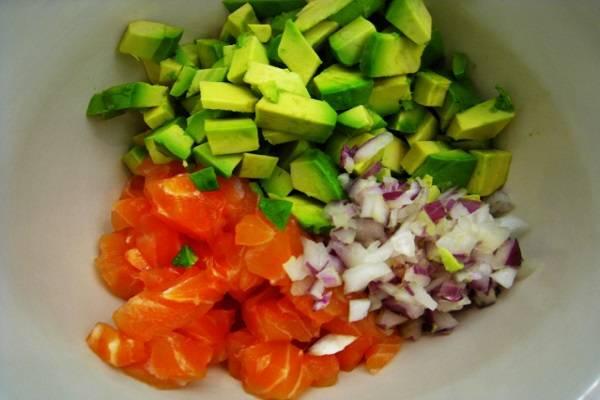 3. Луковицу очистить и нарезать кубиками. В данный рецепт приготовления тарталеток с семгой и авокадо используется фиолетовый лук (белый лук можно предварительно ошпарить кипятком, чтобы ушла лишняя горечь). Соединить авокадо, семгу и лук.