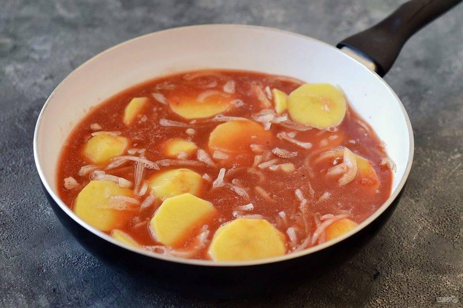 Перелейте томатное пюре в глубокую скороводу, выложите картофель. При необходимости долейте воду, чтобы она полностью покрывала картофель. Варите его на среднем огне почти до готовности. Примерно 15-20 минут.