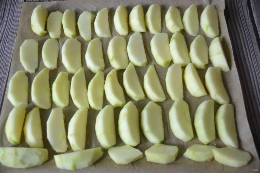 Порежьте яблоки дольками, не слишком тонко, одно яблоко на 8 долек, уложите на пергамент в один слой.